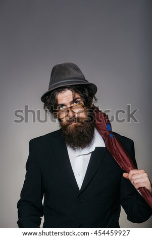 Handsome man bearded hipster male wears vintage hat glasses black suit with umbrella cane on grey wall - stock photo