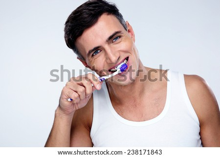 Handsome man brushing his teeth over gray background - stock photo