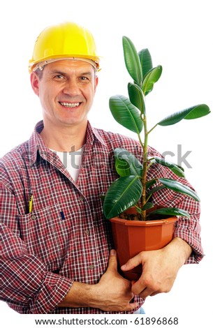 handsome man-builder holding a green plant in a pot - stock photo