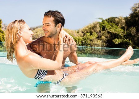 Handsome man carrying his girlfriend in the pool - stock photo