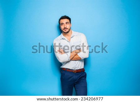 handsome man casual dressed looking up on blue background - stock photo
