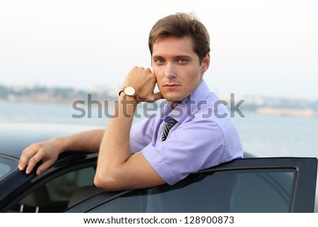 Handsome Man casually leaning against the car, outdoor portrait - stock photo