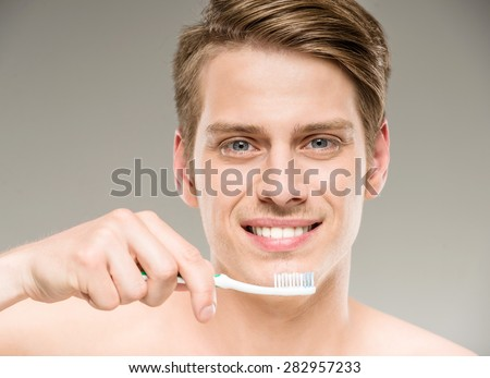 Handsome man cleaning teeth with tooth brush in bathroom. - stock photo
