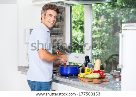 Handsome man cooking at home kitchen smile, prepare food, healthy fresh vegetable diet - stock photo