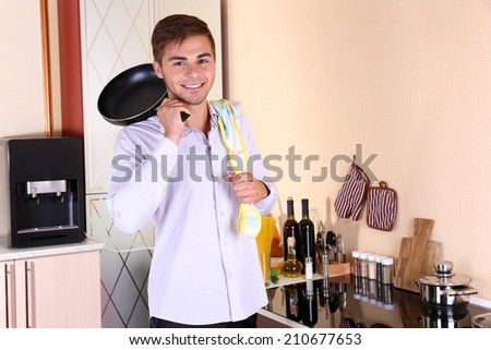 Handsome man cooking in kitchen at home - stock photo