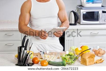 Handsome man cooking in the kitchen at home - stock photo