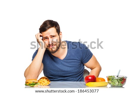handsome man craving after junk food instead of eating healthy food, isolated - stock photo