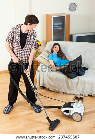 Handsome man doing cleaning during girl with notebook resting over sofa at home - stock photo