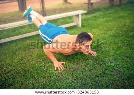 handsome man doing push-ups in park, bodybuilding and training. Fitness concept with shirtless man outdoors, doing exercises - stock photo