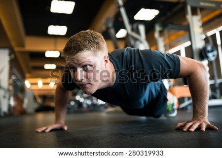 Handsome man doing push-ups in sports club - stock photo