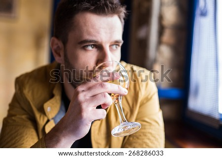 Handsome man drinking a glass of wine - stock photo