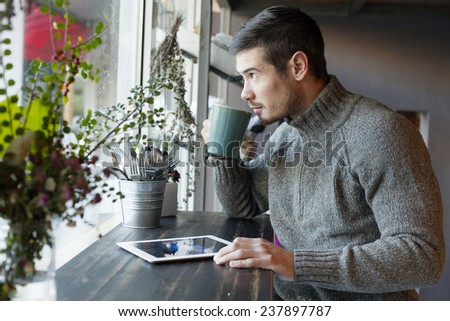 Handsome Man Drinking Coffee And Using Tablet Computer Inside Cafe Bar - stock photo