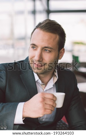 Handsome man drinking espresso in cafe - stock photo
