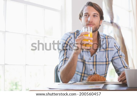 Handsome man drinking orange juice at breakfast at home in the living room - stock photo