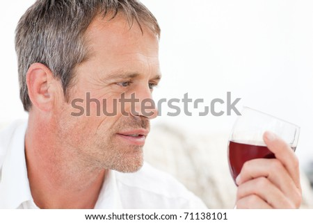 Handsome man drinking some red wine at home - stock photo