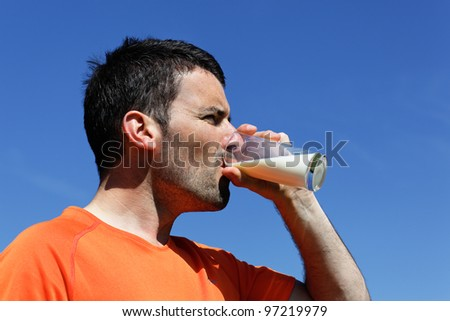 handsome man drinking water in blue sky - stock photo