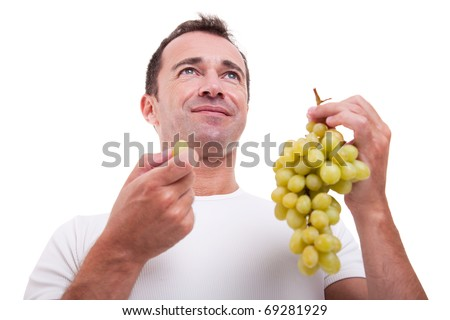 handsome man eating a green grapes, isolated on white background. Studio shot. - stock photo