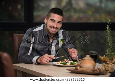 Handsome Man Eating At A Restaurant And Looking Happy - stock photo