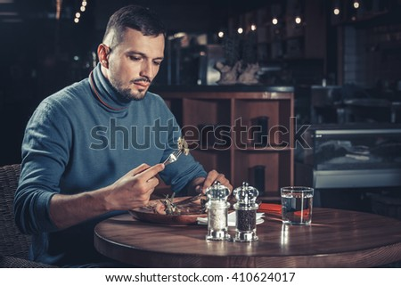 Handsome man eating tasty meat at the restaurant - stock photo