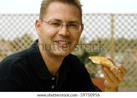 Handsome man eating toast with jam - stock photo
