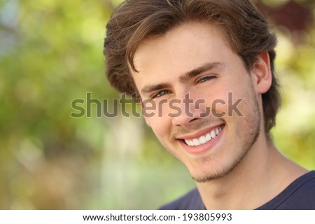Handsome man face with a white perfect smile with a green background - stock photo