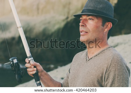 Handsome man fishing during his day off, selective focus - stock photo