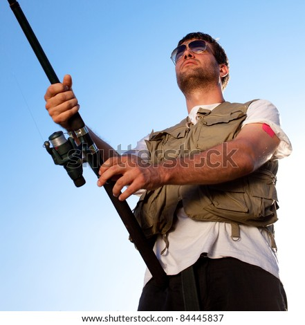 Handsome man fishing. Shot against clear blue sky. - stock photo
