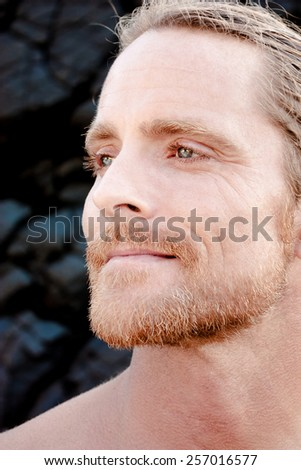 Handsome man gazing into the distance with a gentle smile of pleasure as he reminisces recalling happy memories, close up of his face in side view - stock photo