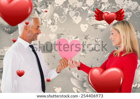 Handsome man getting a heart card form wife against grey valentines heart pattern - stock photo
