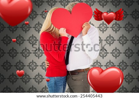 Handsome man getting a heart card form wife against grey wallpaper - stock photo