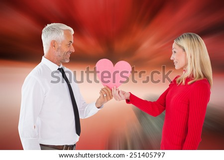 Handsome man getting a heart card form wife against large rock overlooking red sky - stock photo