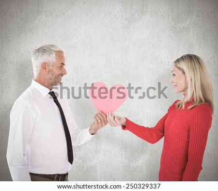Handsome man getting a heart card form wife against weathered surface - stock photo