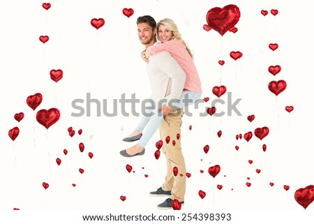 Handsome man giving piggy back to his girlfriend against red heart balloons floating - stock photo
