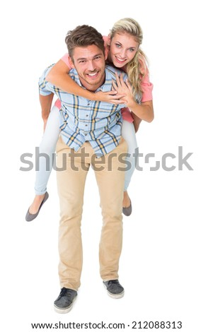 Handsome man giving piggy back to his girlfriend on white background - stock photo