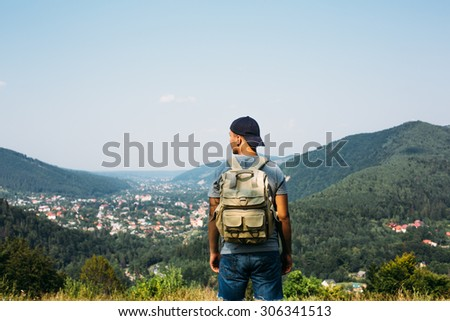 handsome man guy tourist standing alone by the mountain forest landscape during his summer vacation with his backpack back view - stock photo