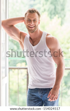 Handsome man. Handsome young man looking at camera and smiling - stock photo