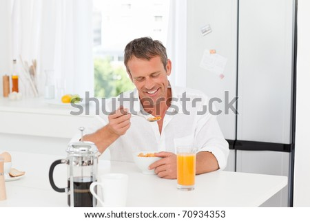 Handsome man having his breakfast in the kitchen at home - stock photo