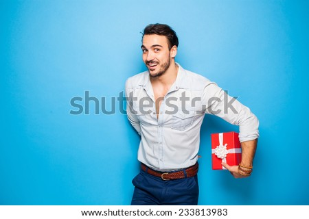 handsome man hiding a christmas gift behind him on blue background - stock photo