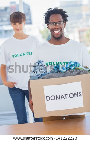 Handsome man holding donation box full of clothes next to a colleague - stock photo