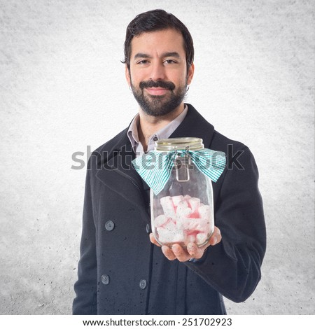 Handsome man holding glass jar with sweets inside - stock photo