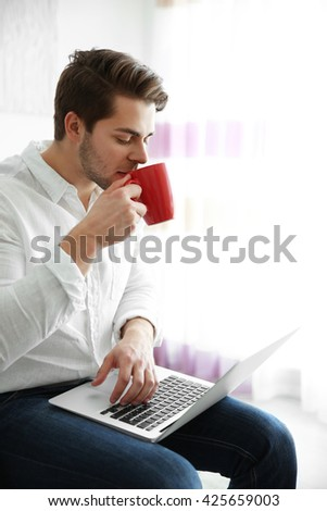 Handsome man holding laptop and drinking coffee in the morning - stock photo