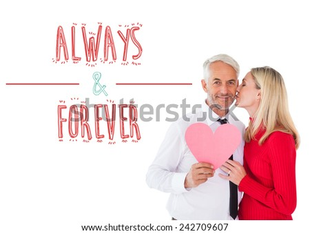 Handsome man holding paper heart getting a kiss from wife against always and forever - stock photo