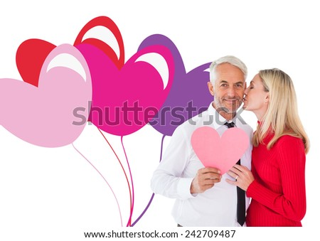 Handsome man holding paper heart getting a kiss from wife against valentines love hearts - stock photo