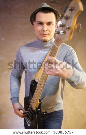 Handsome man in a hat holding an electric guitar in his hands - stock photo
