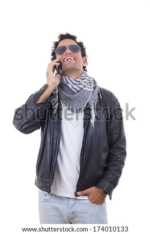 handsome man in a leather jacket talking over phone - stock photo