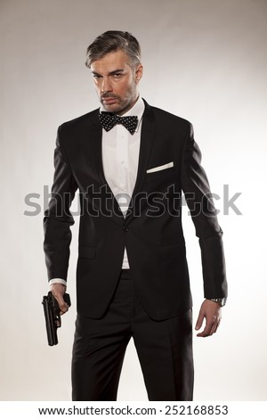 handsome man in a suit with a gun in his hand - stock photo