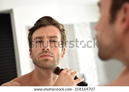Handsome man in bathroom shaving with electric razor - stock photo