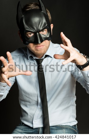 handsome man in blue shirt and batman mask angry at black background - stock photo