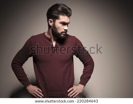 Handsome man in burgundy sweater holding his hands to his waist, looking away from the camera - stock photo
