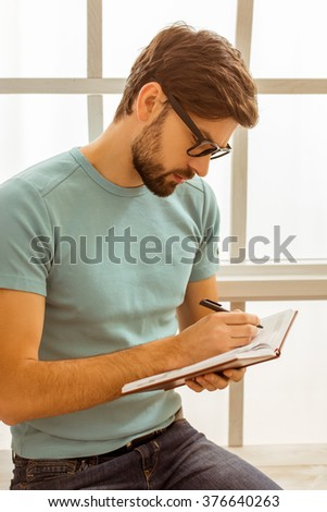 Handsome man in casual clothes and eyeglasses making notes in the notebook while sitting near the window - stock photo